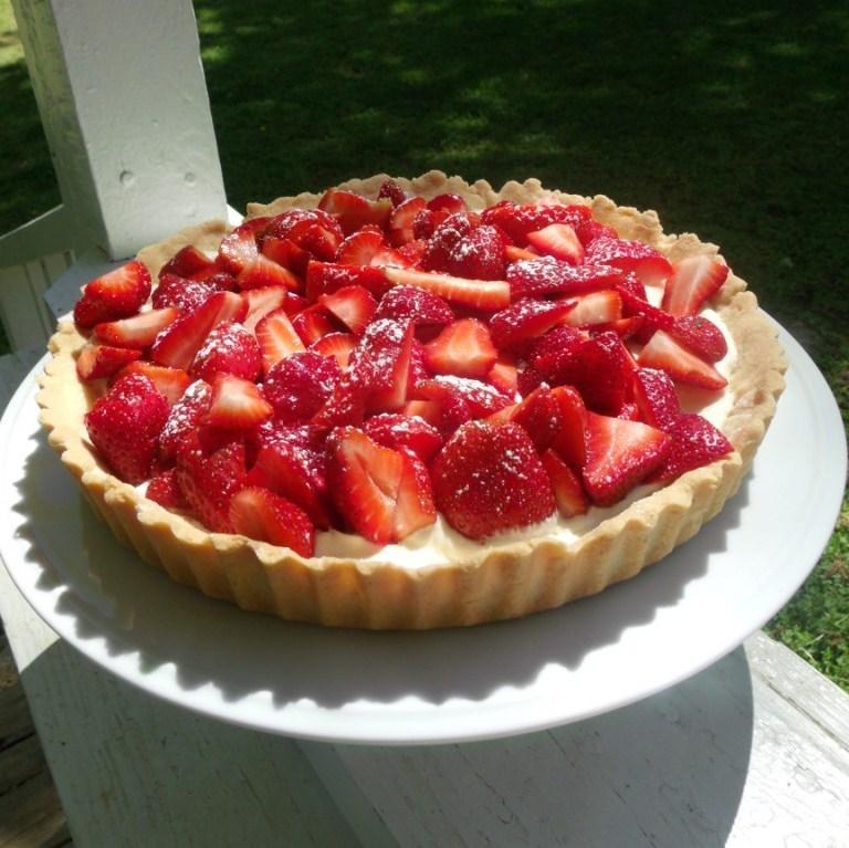strawberry mascarpone tart on a white plate outside