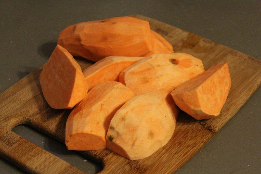 sweet potatoes peeled and cut on cutting board