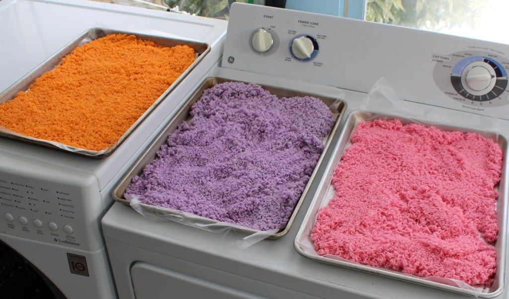 orange, purple and pink rice on separate baking pans
