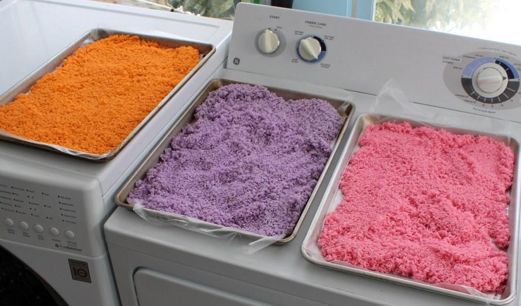 orange, purple and pink rice on separate baking pans