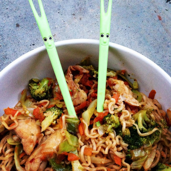 chopsticks in bowl of noodles with chicken and vegetables