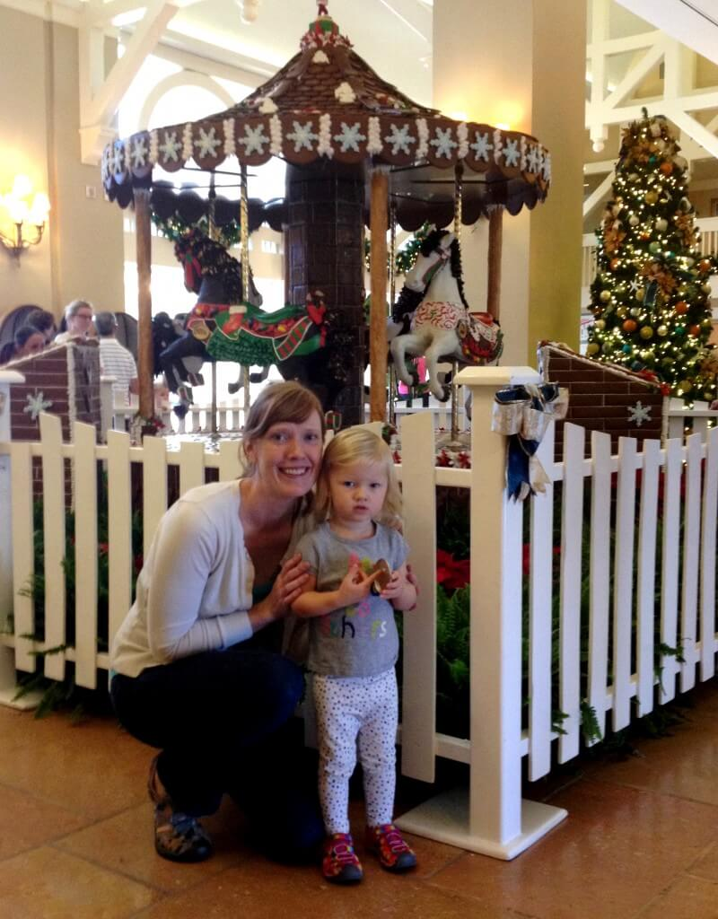 mom and daughter in front of a carousel