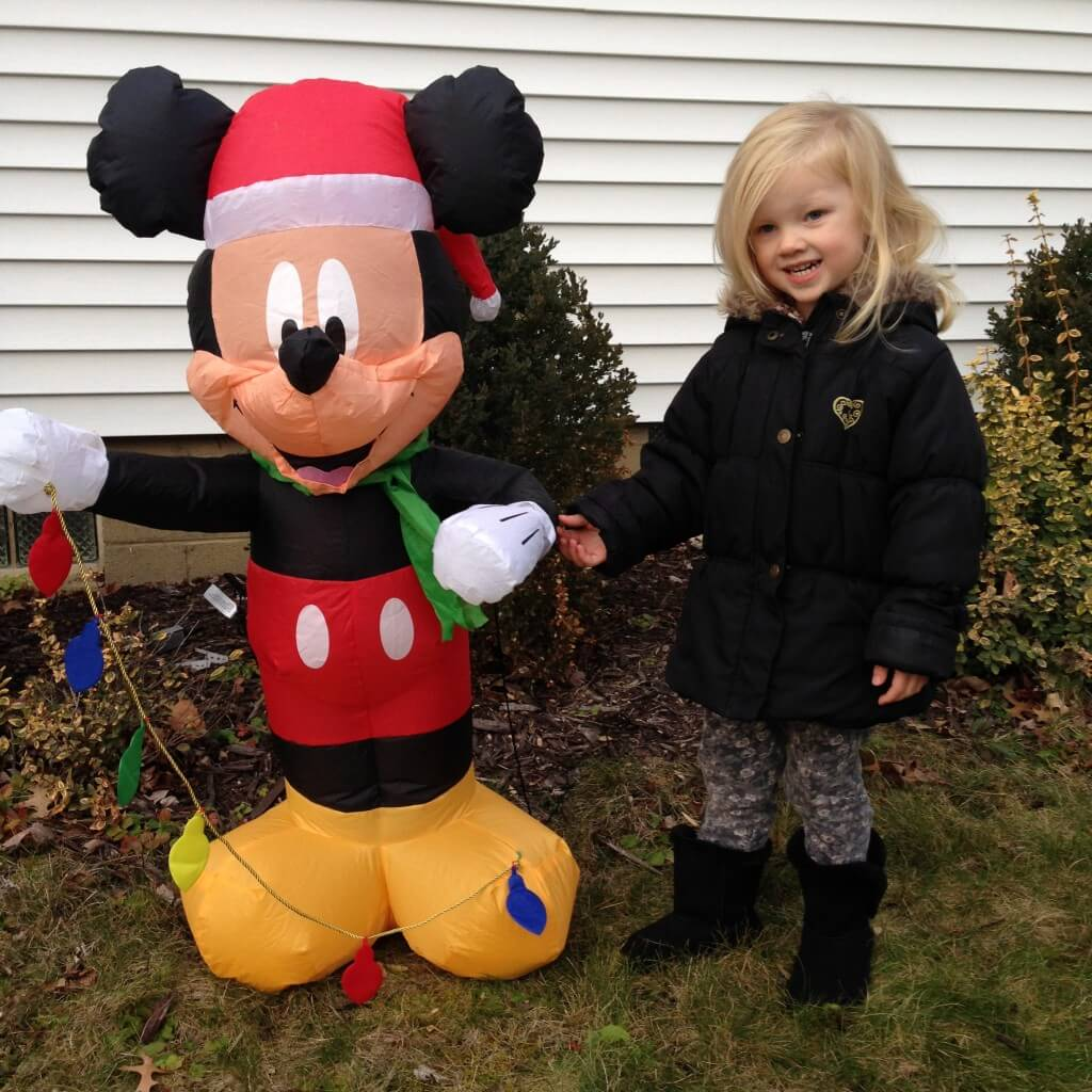 little girl next to inflatable christmas Mickey
