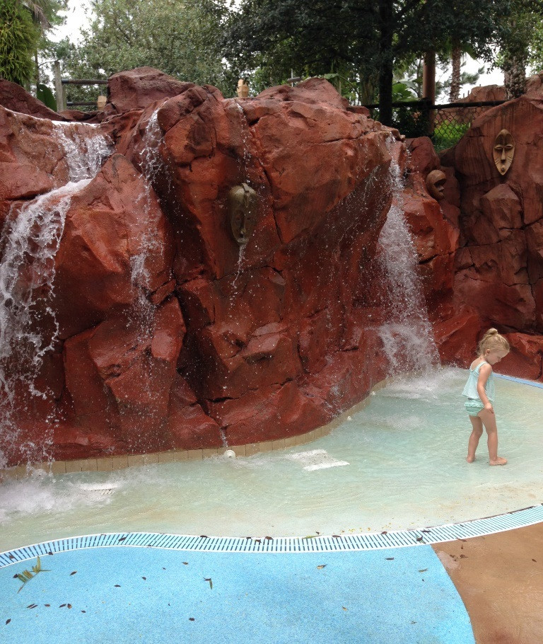 little girl playing in the rock waterfall area
