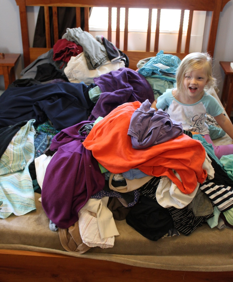little girl in a pile of clothes on a bed