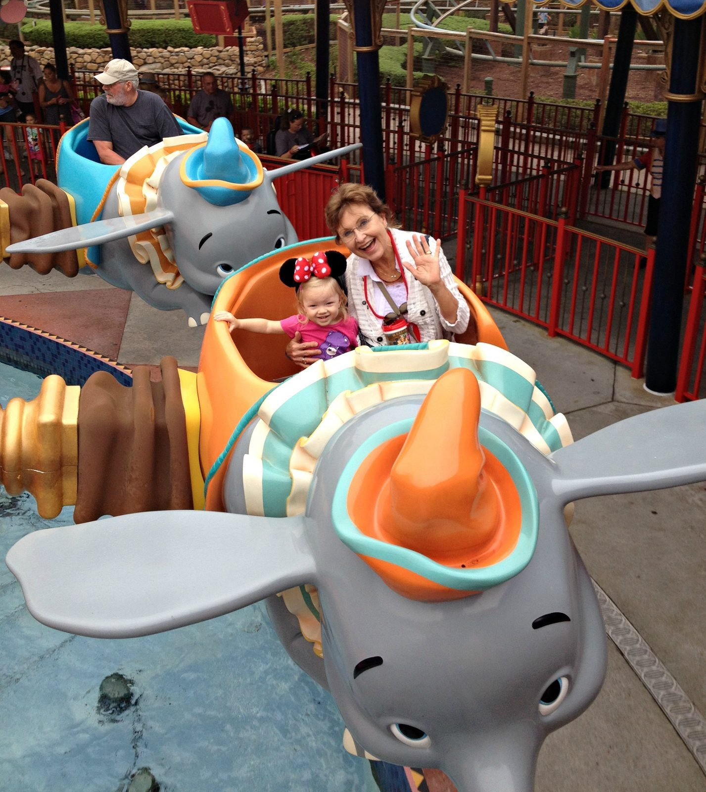 little girl and grandmother riding the disney dumbo ride