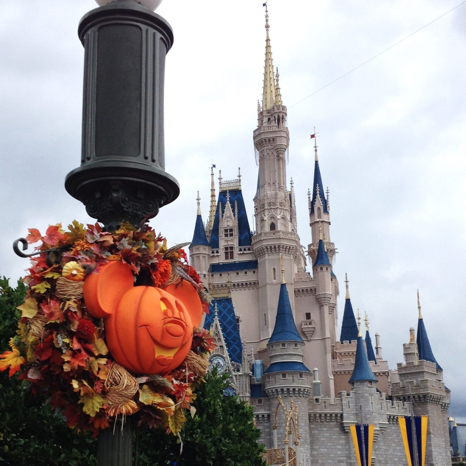 halloween decor on lamp post with cinderella's castle in the background