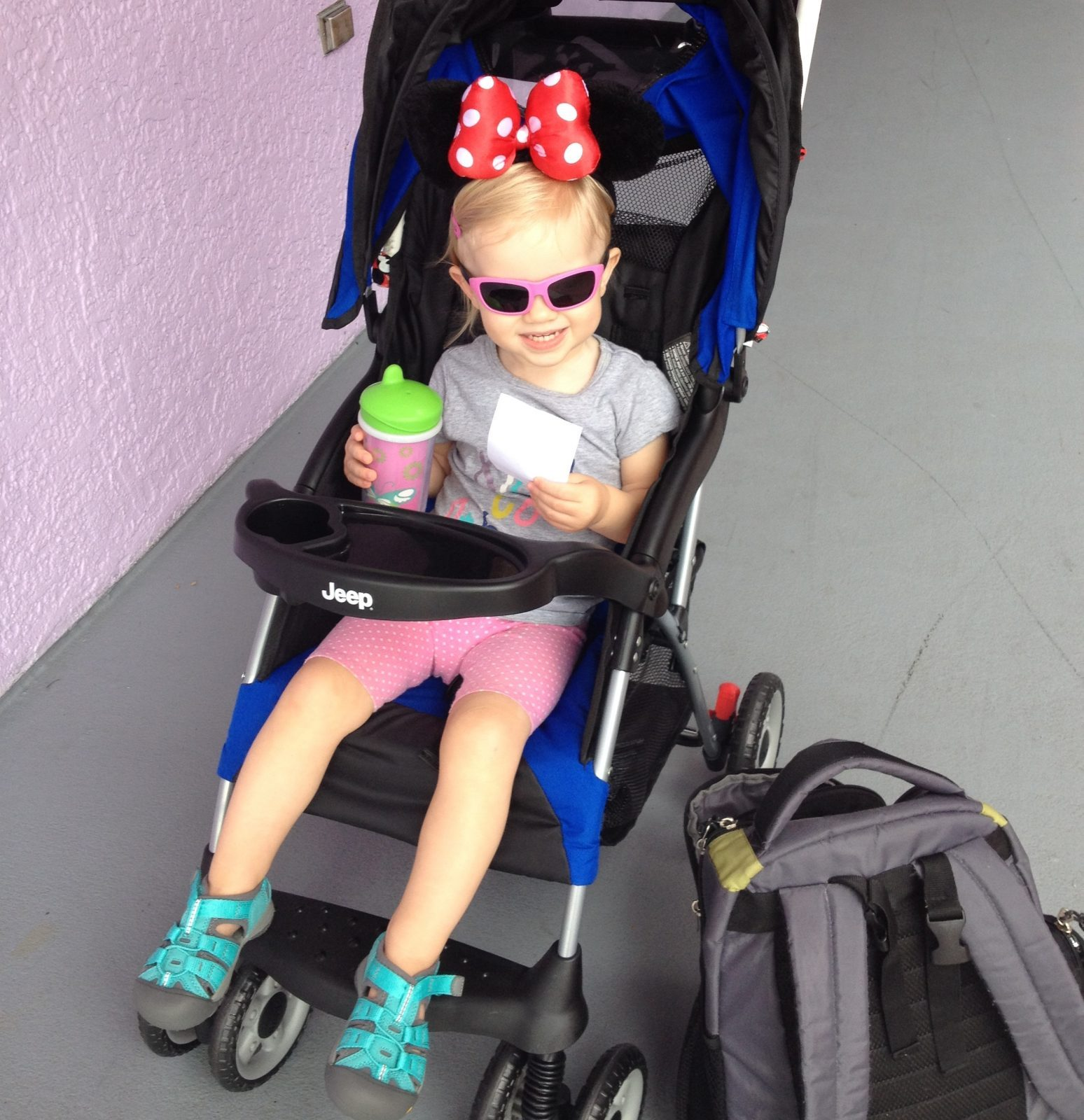 little girl with minnie ears sitting in a stroller