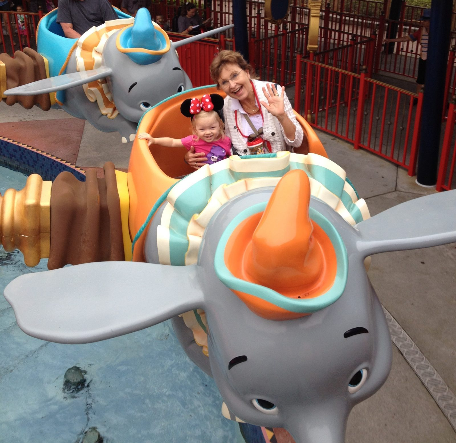 little girl and grandmother riding dumbo ride at magic kingdom