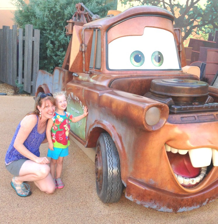 mom and daughter posing with Mater from Cars
