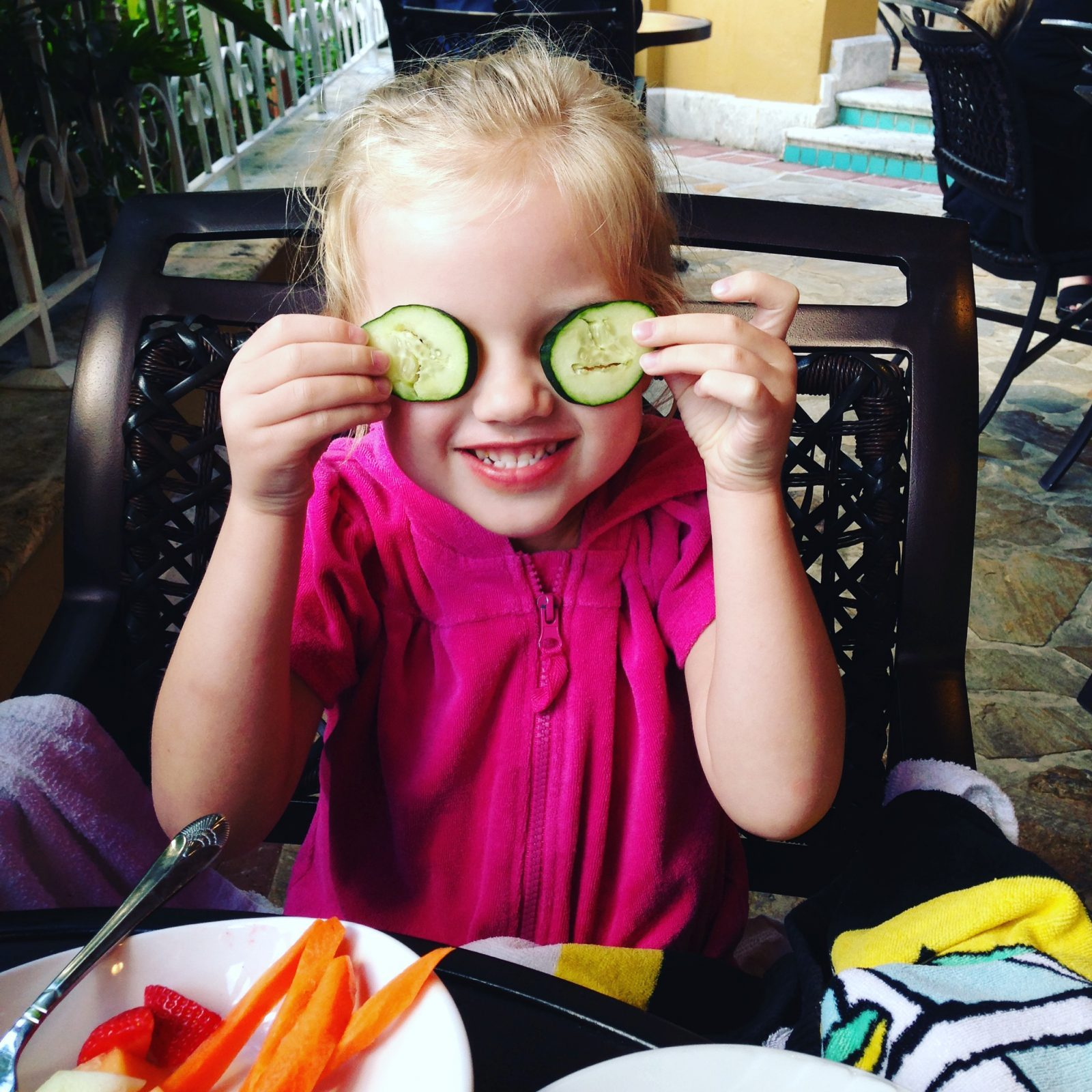 little girl playing with cucumbers over her eyes