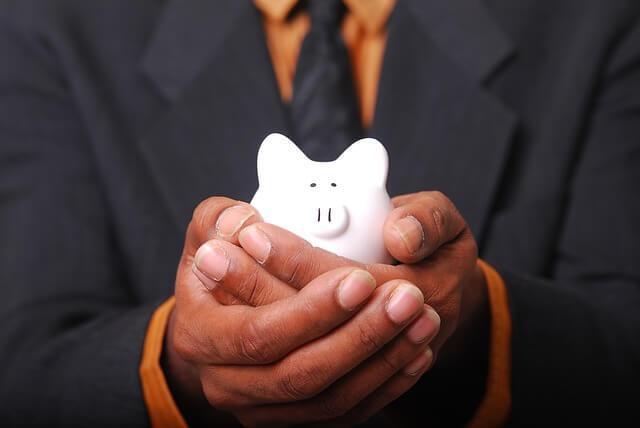 man holding a small piggy bank