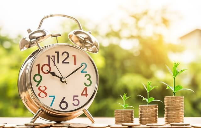 coins with plants growing on top and a clock
