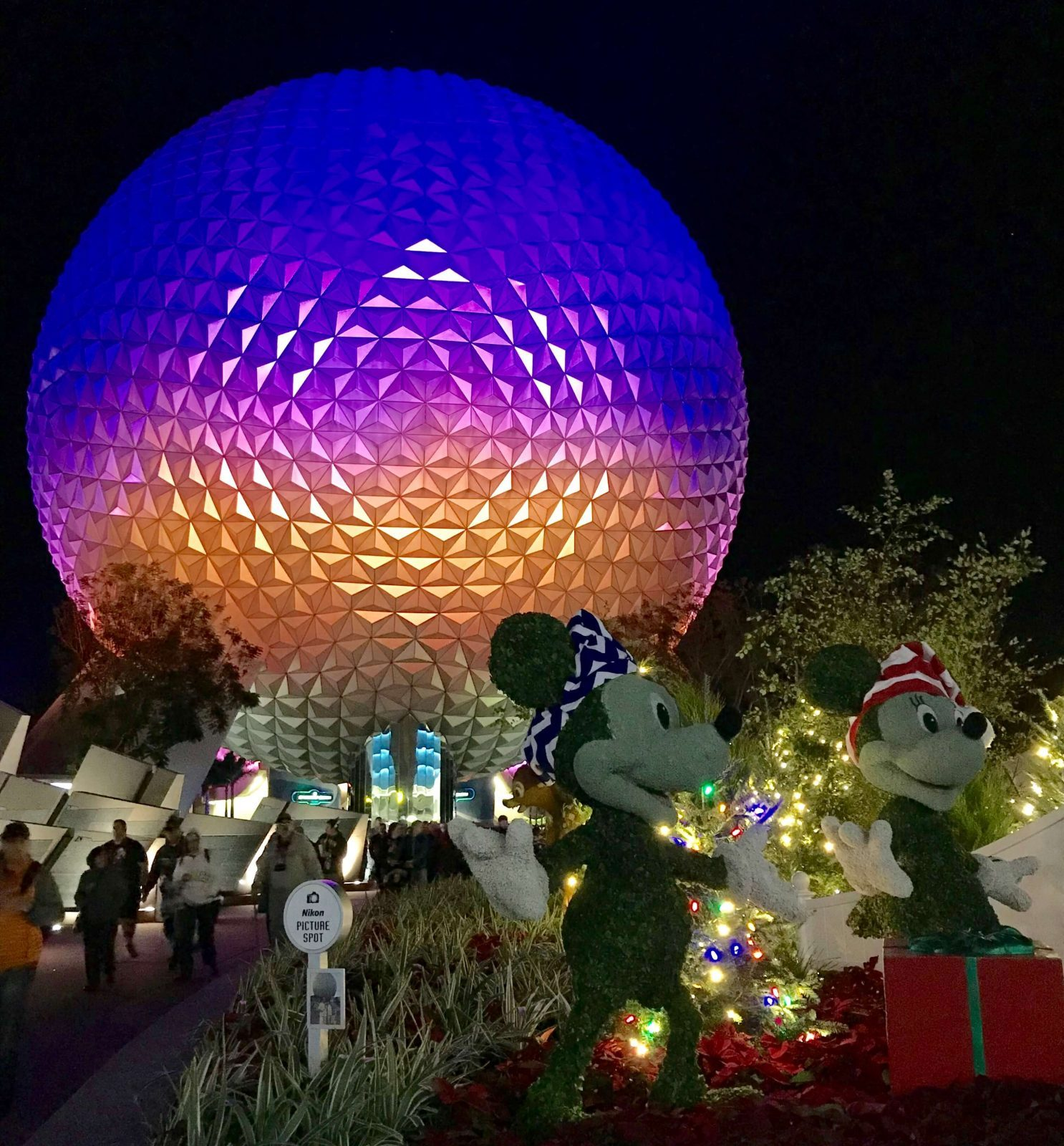 mickey and minnie mouse in front of Epcot geosphere