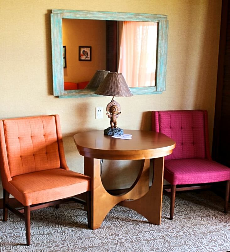sitting area with orance and pink chair, brown table and lamp, and blue mirror
