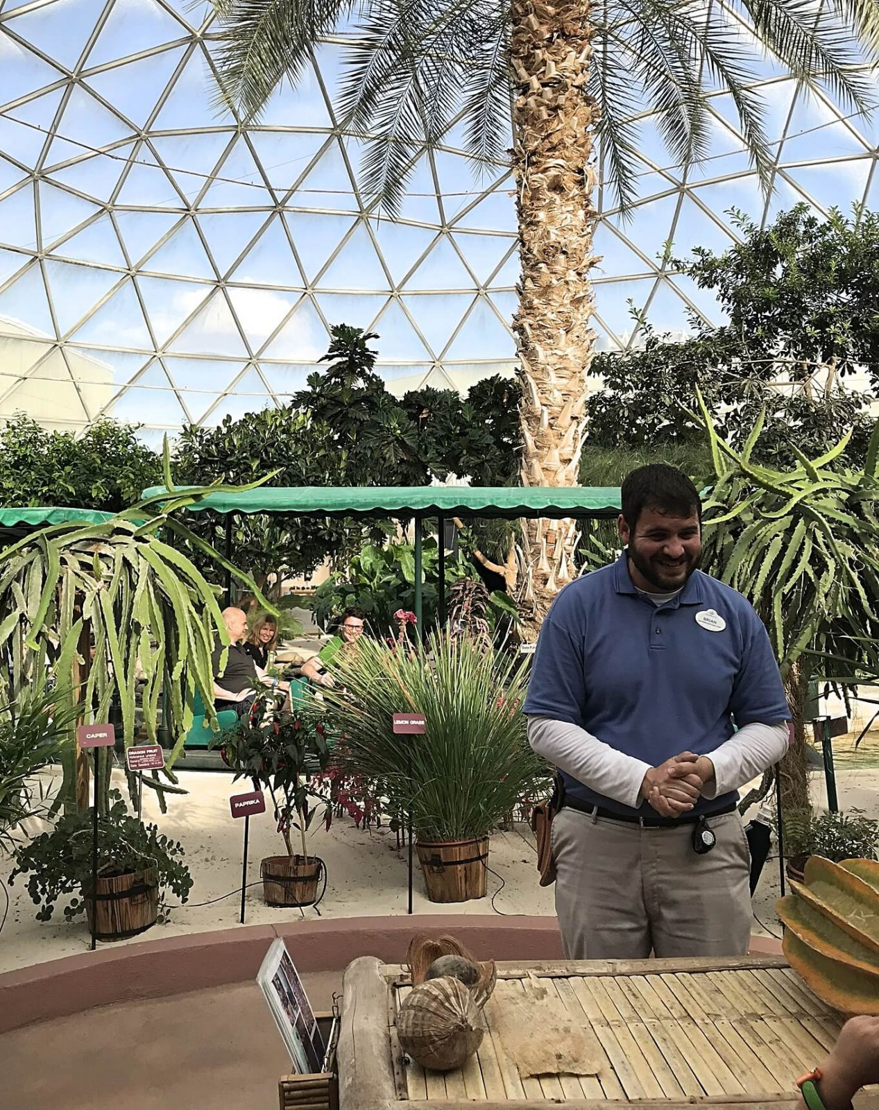 disney cast member giving a tour of the greenhouse with the living with the land ride in the background