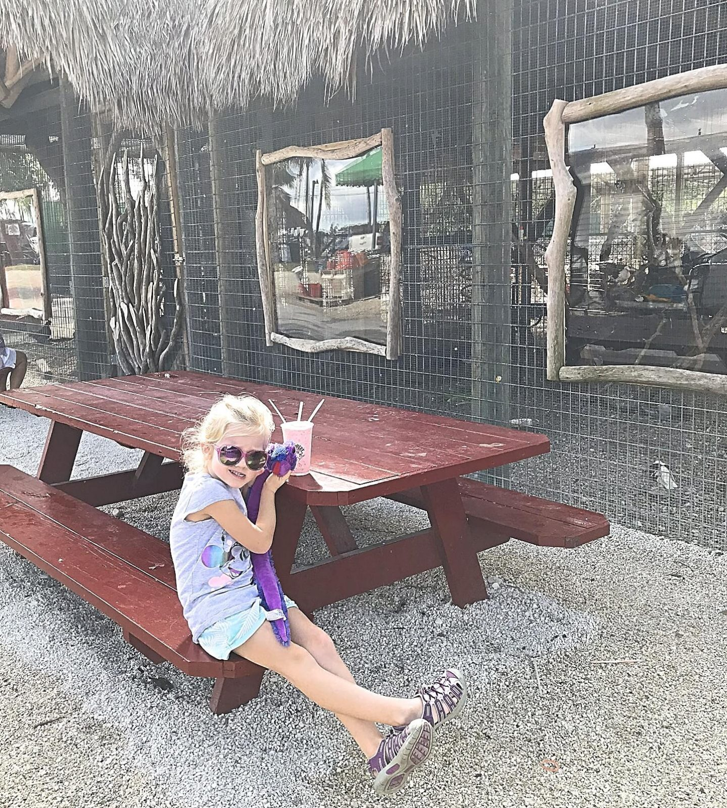 little girl enjoying a smoothie at a picnic table