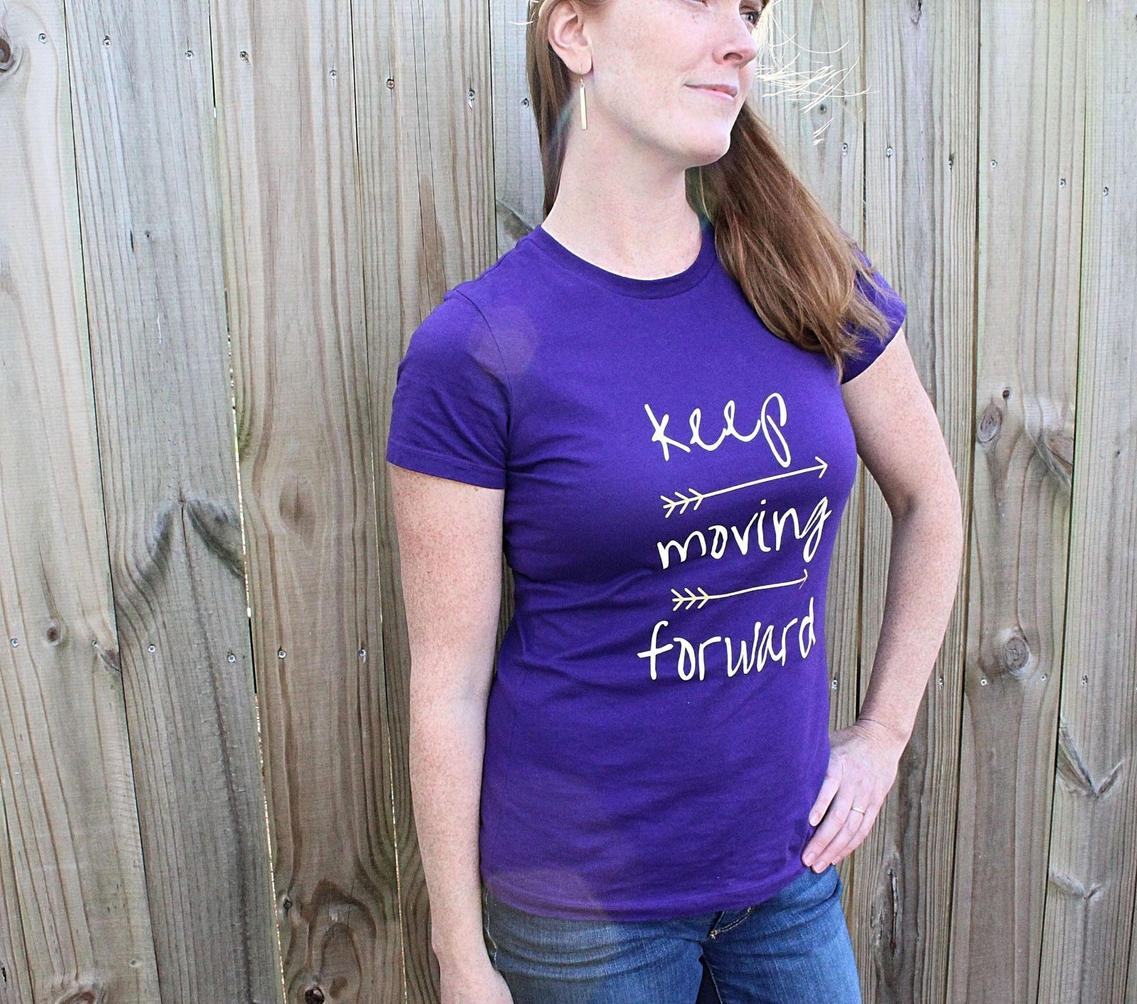 Model posing in front of a wood fence in the blue keep moving forward tshirt