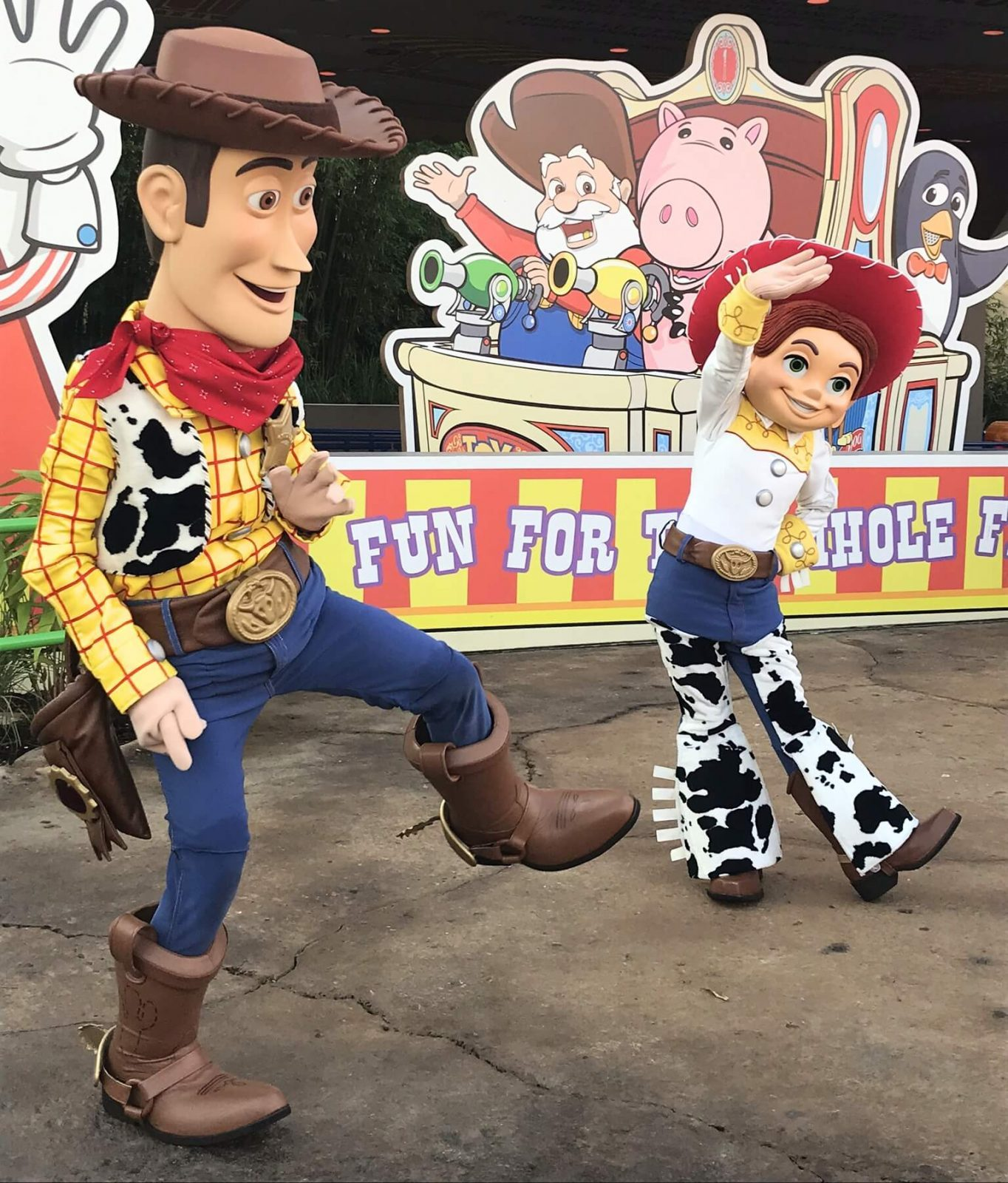 disney characters, woody and jessie walking around in toy story land