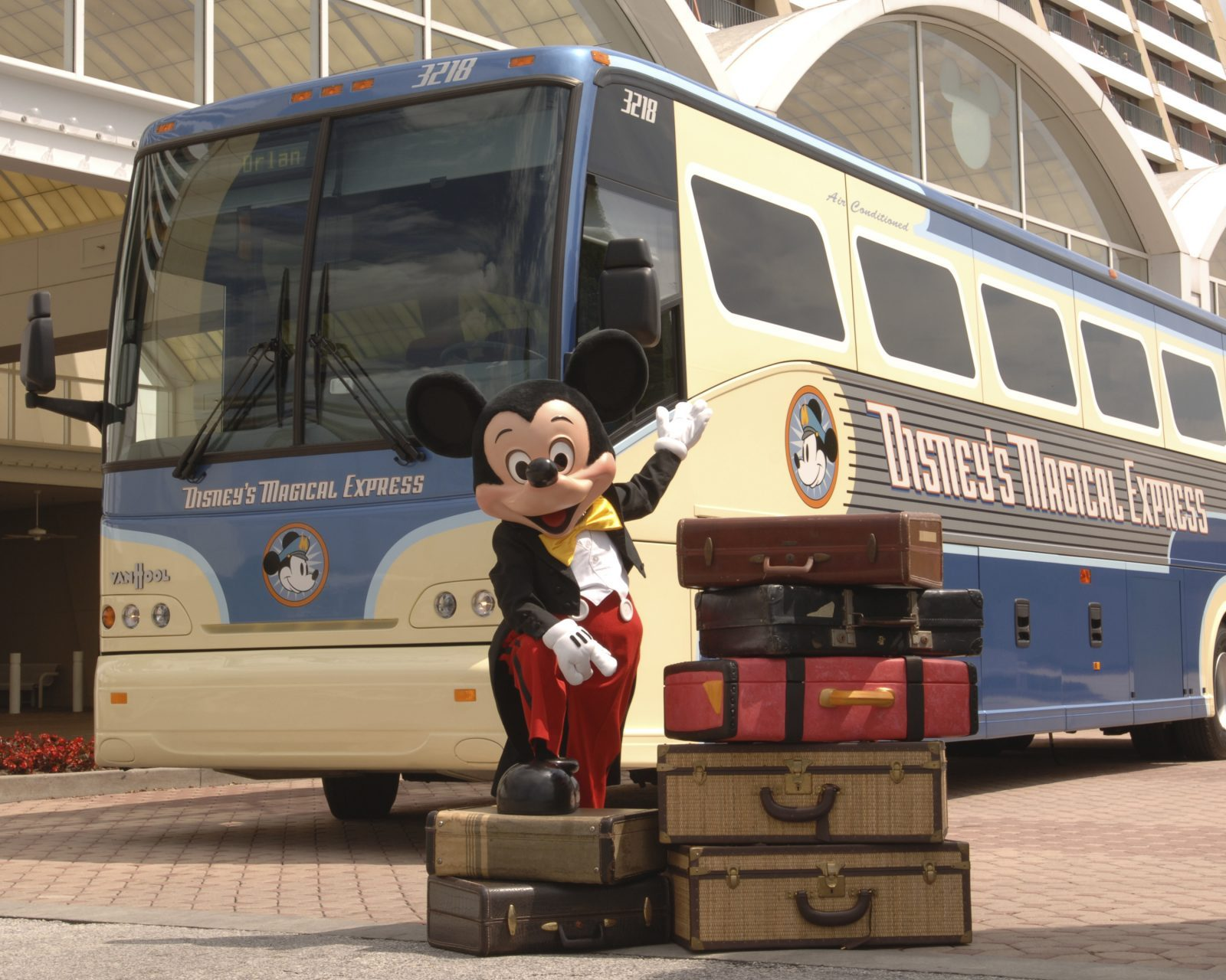 Disney Magical Express bus and Mickey Mouse with luggage
