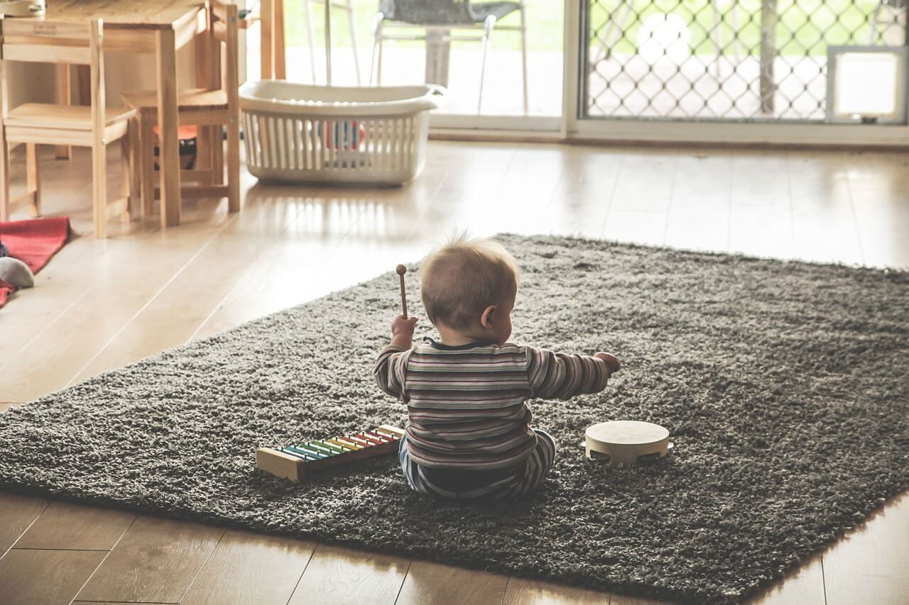 baby playing with toys on a rug