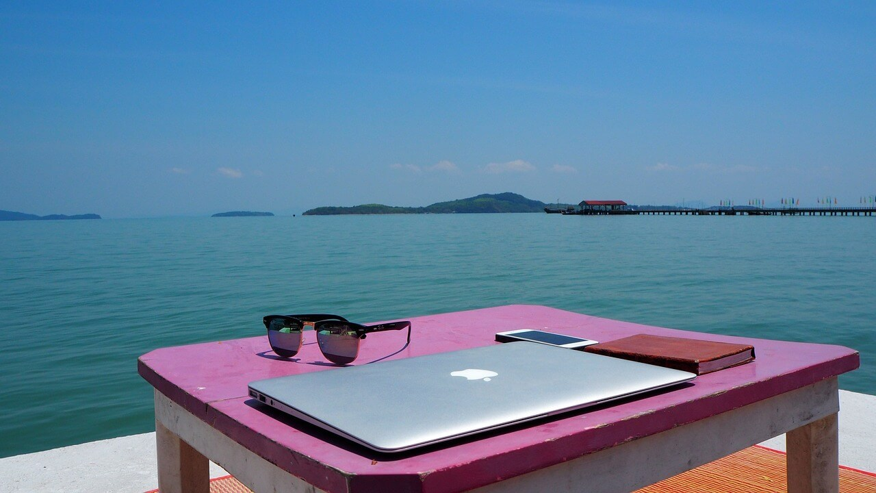 laptop on a table with the ocean in the background