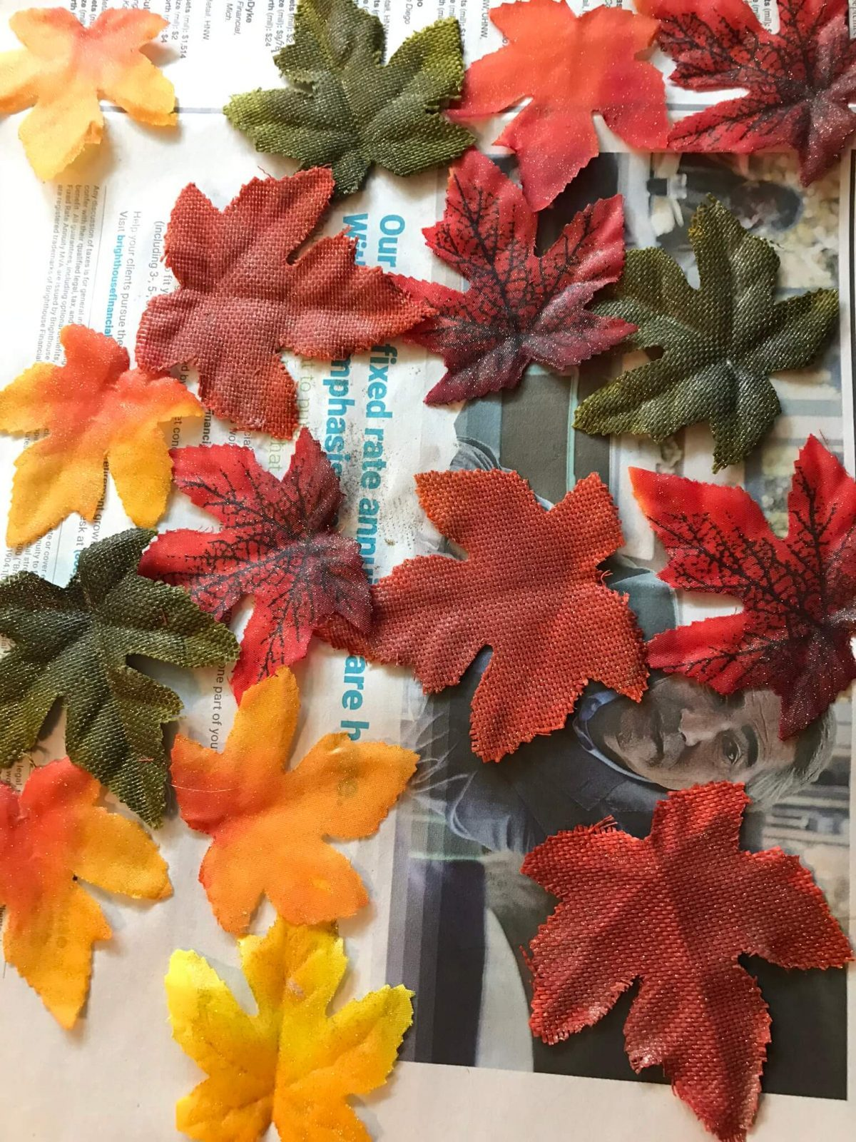 fake leaves spread across newspaper