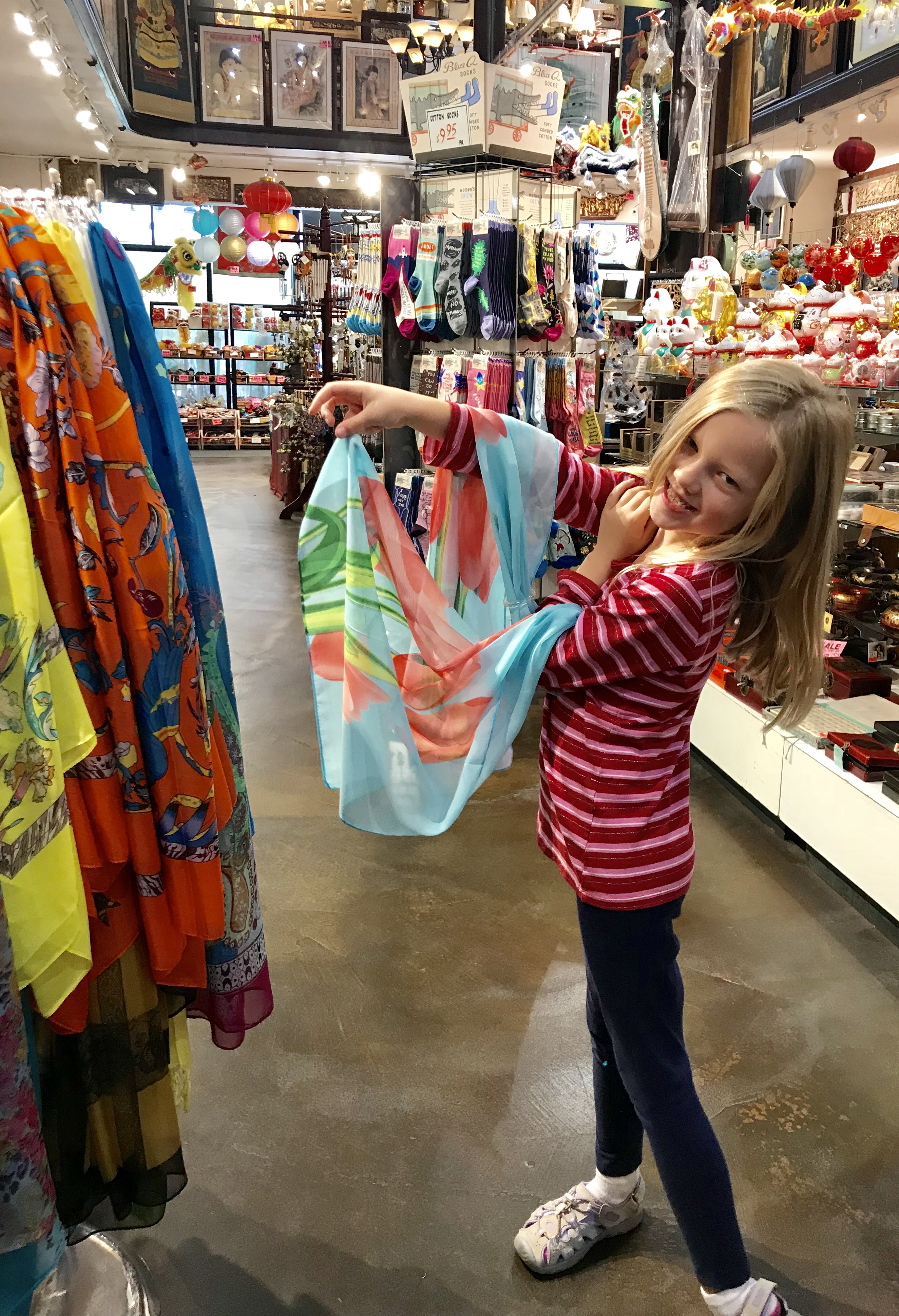 little girl playing with scarf in souvenir shop