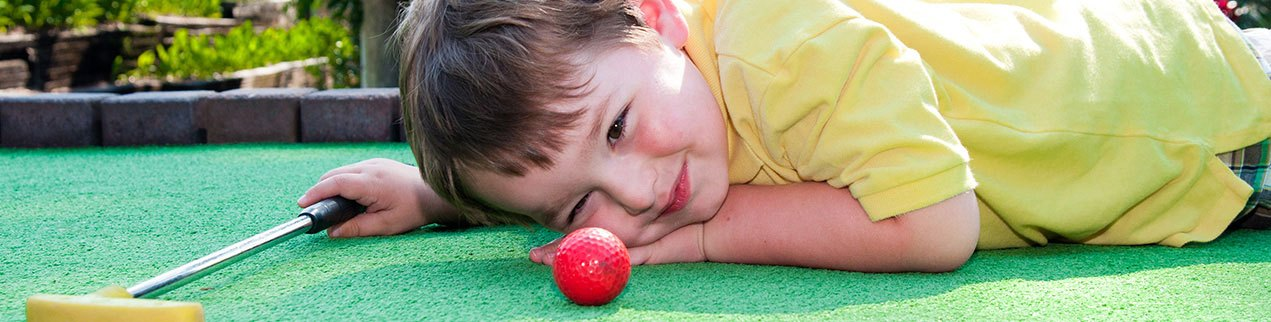 Little boy playing mini golf - things to do in Pigeon Forge TN