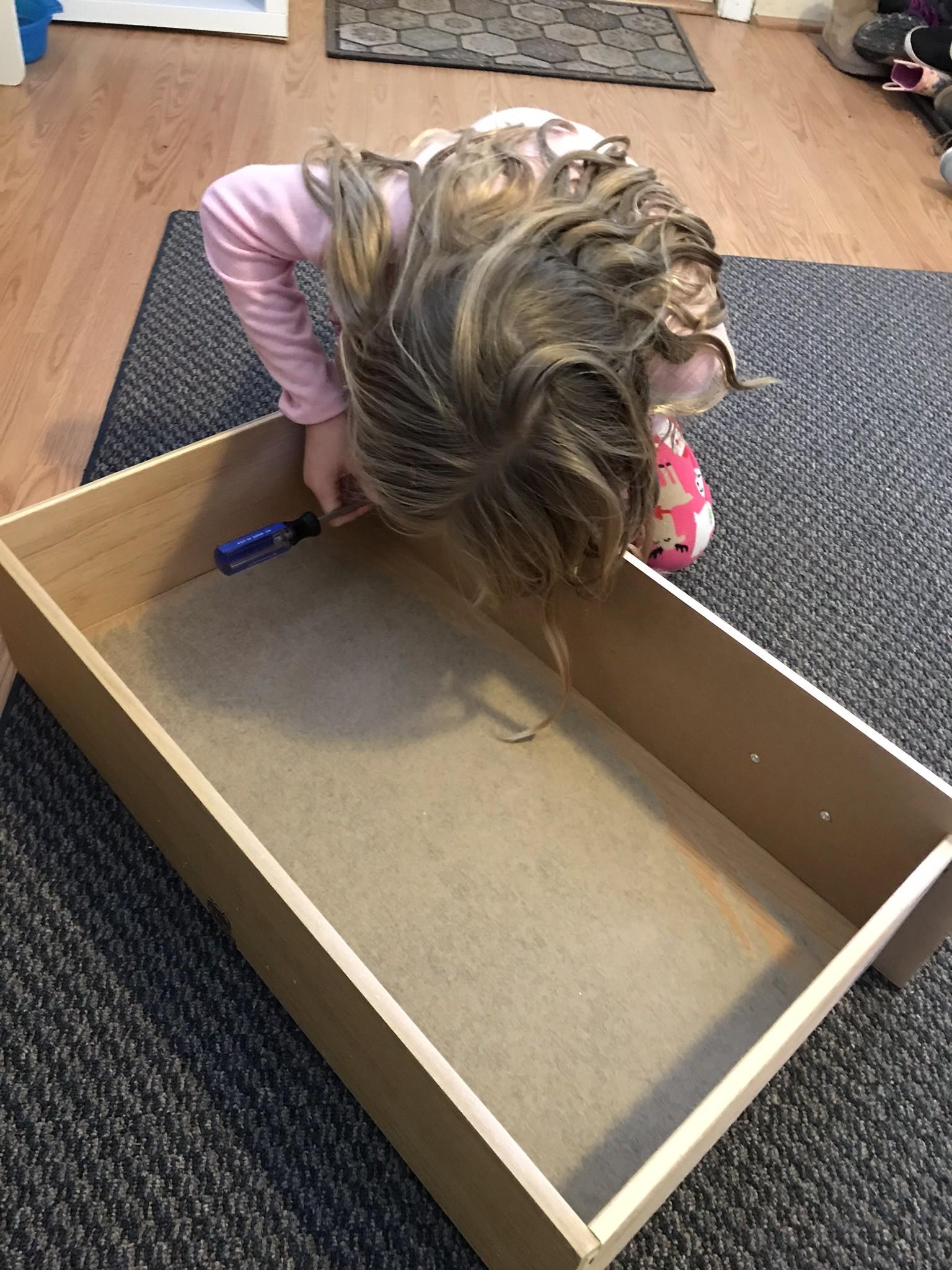 little girl installing the drawer hardware