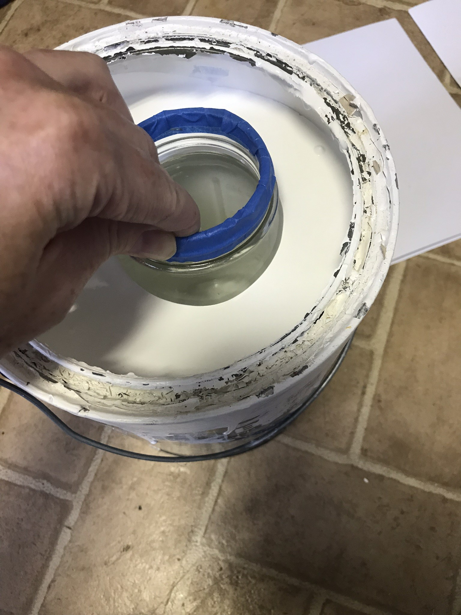 dipping the mason jar in the paint can