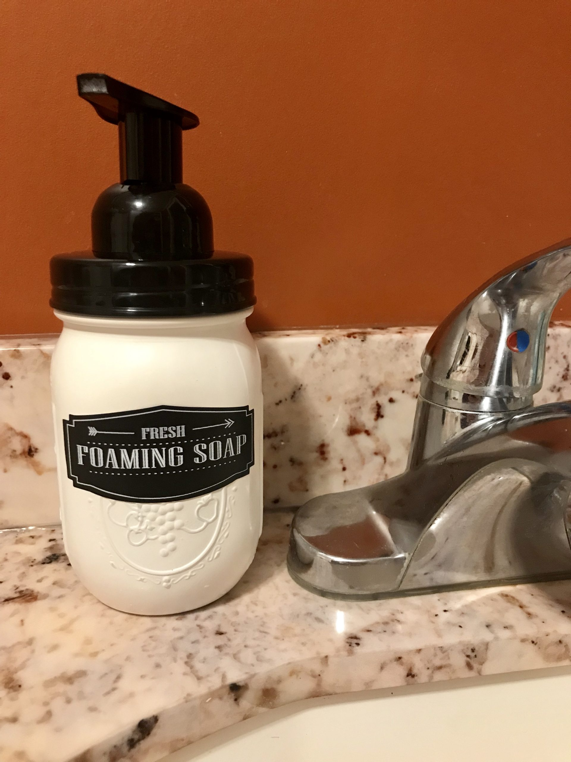 completed DIY foaming hand soap dispenser by the sink