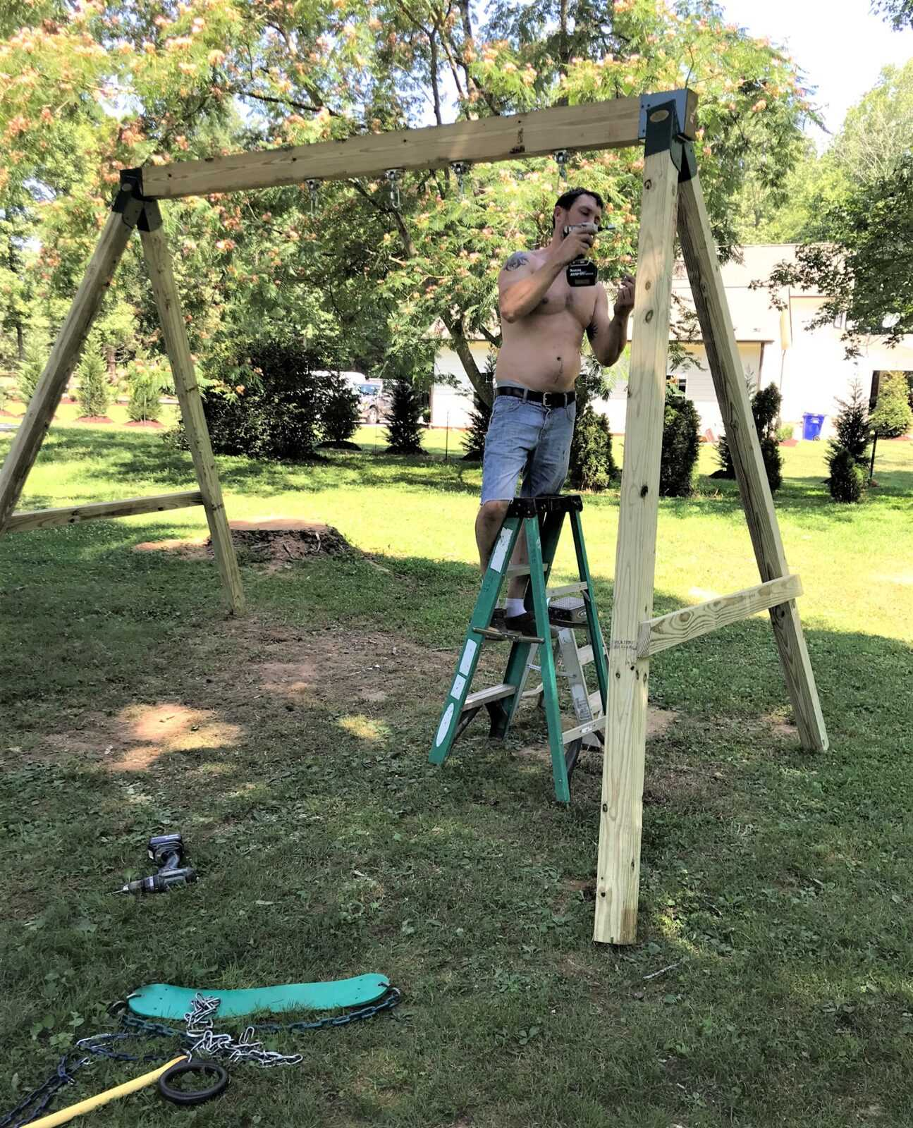 man with drill assembling swing set