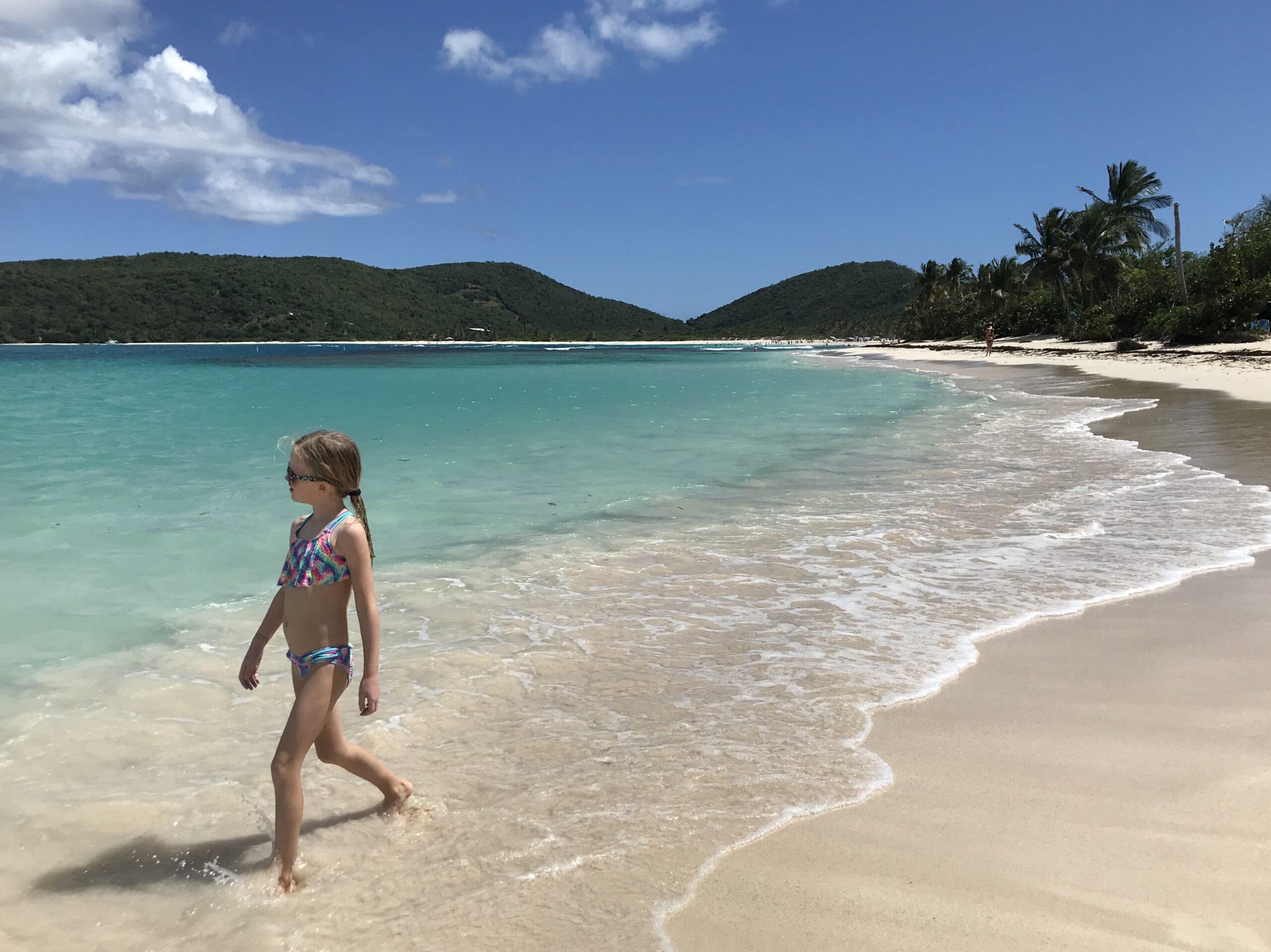 girl walking on flamenco beach in culebra